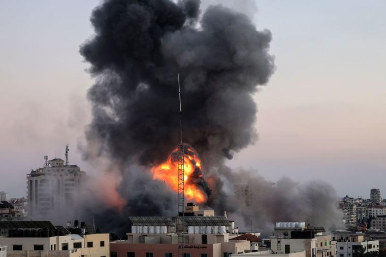 Black smoke billows after an Israeli airstrike on Gaza City targeted the Ansar compound, linked to the Hamas movement, in the Gaza Strip on May 14. Israel targeted Gaza and deployed extra troops to the border as Palestinians fired barrages of rockets back, with the death toll in the enclave on the fourth day of conflict climbing to more than 100.