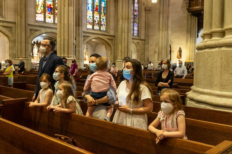 A family prays during St. Patrick's Cathedral Sunday first public Mass since March when pandemic stopped large gatherings.