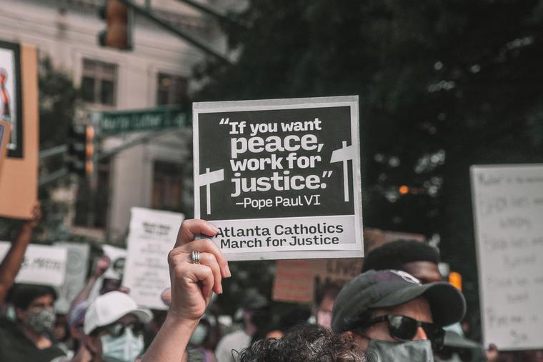 A participant holds up a sign with a quote from Pope St. Paul VI at a June 2020 rally in Atlanta.