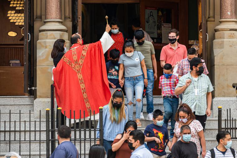 People exit Our Lady of Guadalupe Shrine Catholic church on May 23, 2021 in New York City. On May 19, all pandemic restrictions, including mask mandates, social distancing guidelines, venue capacities and restaurant curfews were lifted by New York Governor Andrew Cuomo.