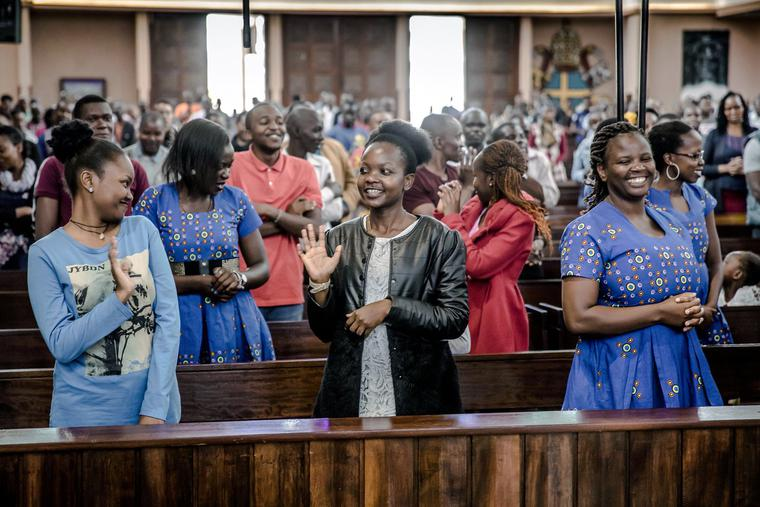 Catholics exchange the sign of peace without shaking hands during a Sunday Mass at Holy Family Minor Basilica in Nairobi, Kenya, on March 22, 2020.