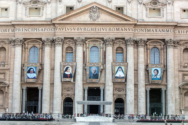 Banners with the official images of (L to R) Sister Irmã Dulce Pontes, Mother Giuseppina Vannini, John Henry Newman, Mother Mariam Thresia and Marguerite Bays hang on the facade of St. Peter's Basilica Oct. 10, 2019, three days before their canonization.
