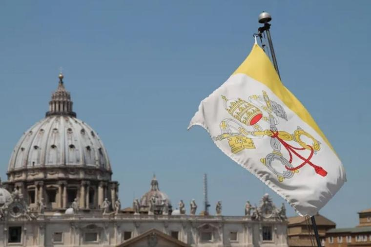 A Vatican City flag flies in view of St. Peter's Basilica in Rome.