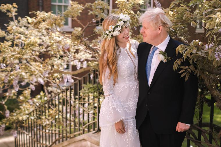 In this handout image released by 10 Downing Street, Prime Minister Boris Johnson poses with his wife Carrie Johnson in the garden of 10 Downing Street following their wedding at Westminster Cathedral, May 29, 2021 in London, England.