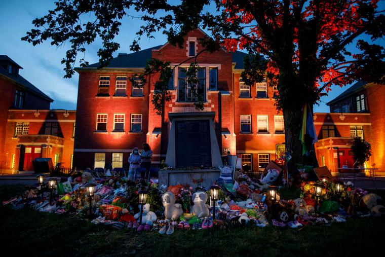 A makeshift memorial to honour the 215 children whose remains have been discovered buried near the facility is seen as orange light drapes the facade of the former Kamloops Indian Residential School in Kamloops, British Columbia, Canada, on June 2, 2021.