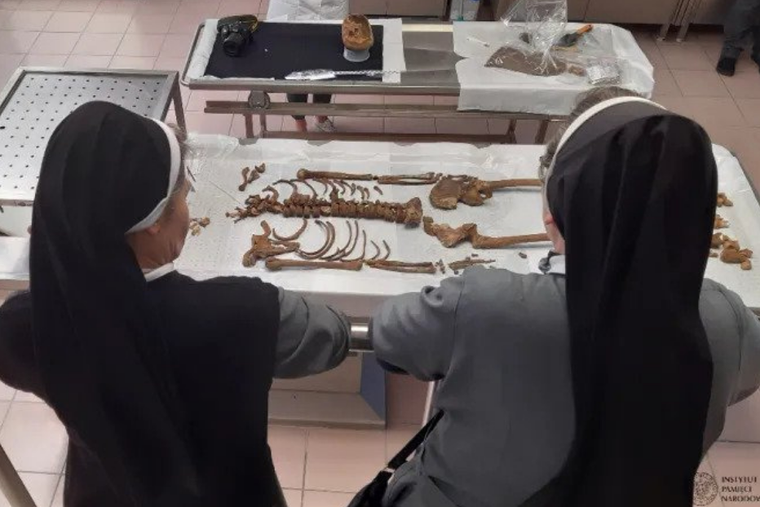 Religious sisters view remains discovered at a site in Gdańsk, northern Poland.