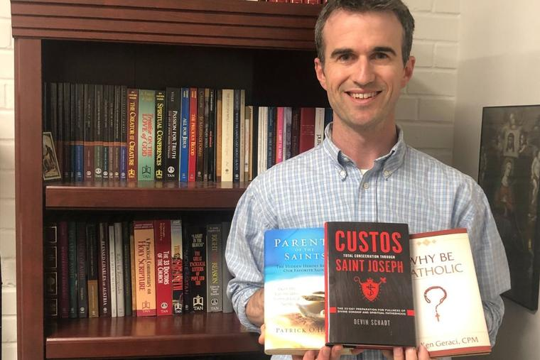 Patrick O'Hearn, who recently took the helm at TAN Books, holds several of the Catholic publisher's latest titles in his office.