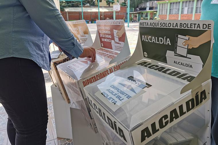A woman inserting her vote into a ballot box, Mexico City, 6 June 2021.