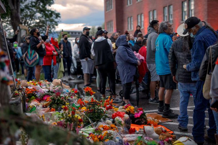 People gather outside the former Kamloops Indian Residential School as they welcome a group of runners from the Syilx Okanagan Nation taking part in The Spirit of Syilx Unity Run, following the discovery of the remains of 215 children buried near the facility, in Kamloops, British Columbia, Canada, on June 5, 2021.