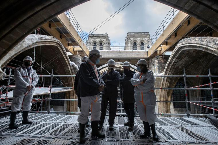 French President Emmanuel Macron (3rd L), the architecte in charge of the restoration Philippe Villeneuve (2nd R), Paris' mayor Anne Hidalgo (R) and Paris' Archbishop Michel Aupetit (2nd L), tour the scaffolding under the vault of Notre-Dame de Paris Cathedral during a visit marking two years since the blaze that made the spire collapsed and destroyed much of the roof, in Paris on April 15, 2021.