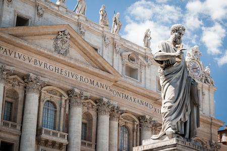 Statue of St. Peter with the facade of St. Peter's Basilica in the background.