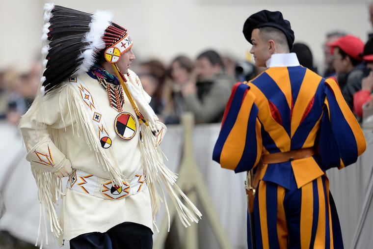 A Native American man wearing traditional regalia walks past a Swiss Guard during Pope Francis' weekly general audience in St. Peter's Square at the Vatican on April 27, 2016.