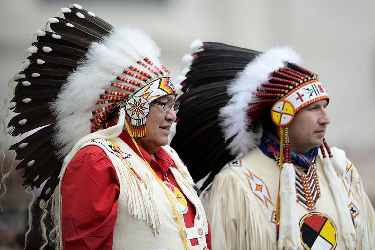 Two Native Americans faithful wearing traditional regalia stand during Pope Francis weekly general audience in St Peter's square at the Vatican on April 27, 2016.