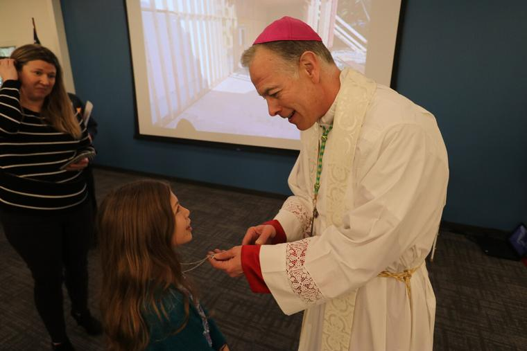 rchbishop Alexander K. Sample blesses a rosary for a girl Queen of Peace Parish in Salem, Oregon in 2020.