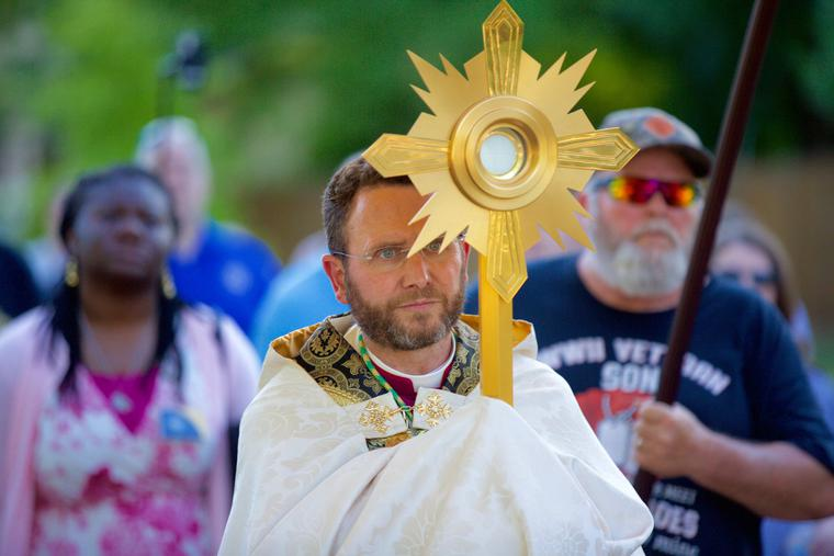 Bishop Andrew Cozzens carries the Eucharist in a monstrance during a procession June 19 at an event called Catholic Father's Day. After Mass at Maternity of Mary in St. Paul, the 1.5-mile procession made a trip from the church to Lake Como and back.