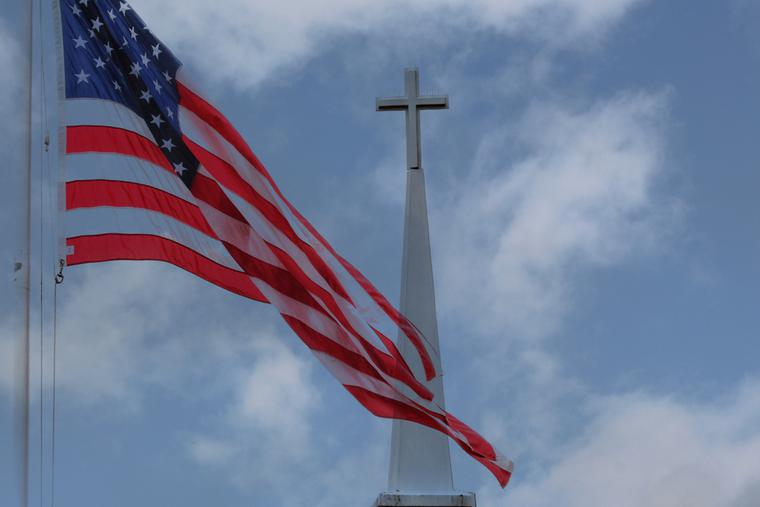 An American flag flies in front a church steeple in the Midwest.