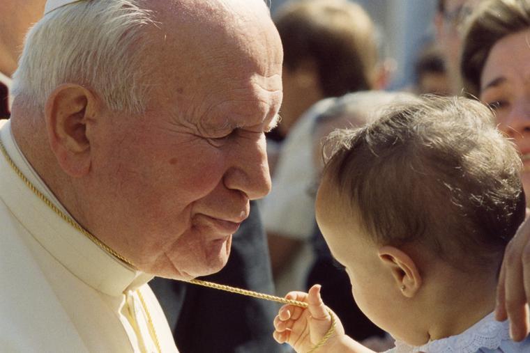Pope John Paul II embracing a child on September 16, 1998.