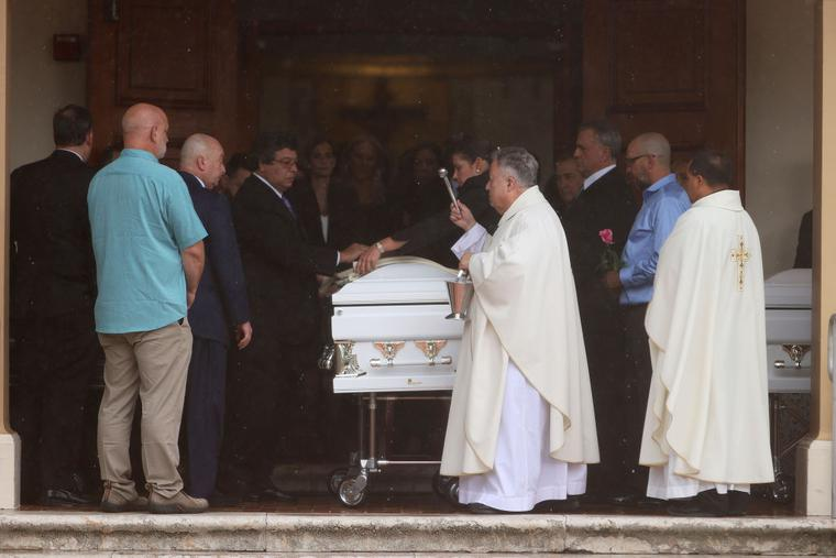 Father Juan Sosa blesses the caskets during the July 6 funeral in St. Joseph Catholic Church for Anaely Rodriguez, her husband, Marcus Guara, and their daughters, Lucia Guara and Emma Guara, after the family was killed in the partially collapsed 12-story Champlain Towers South condo in Miami Beach, Florida.
