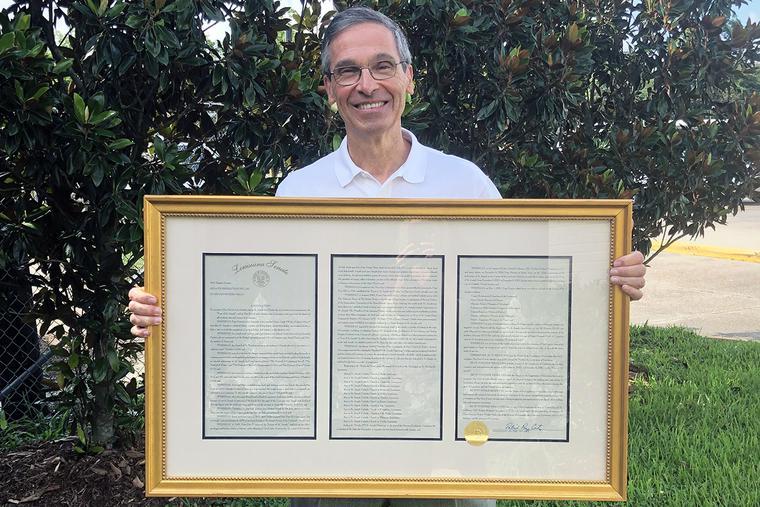 Louisiana Sen. Fred Mills, Jr. holds a copy of the Louisiana Senate's St. Joseph Resolution.