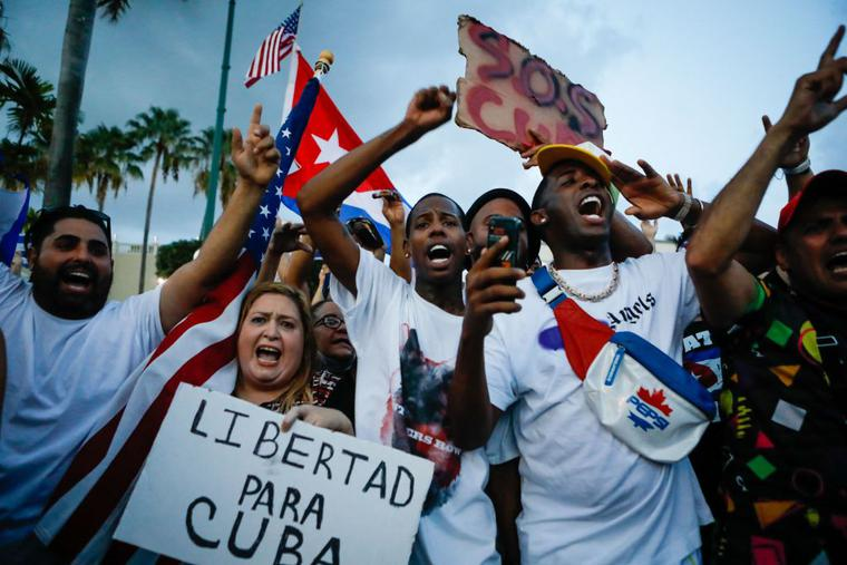 """A woman holds a placard reading """"Freedom for Cuba"""" as others demonstrate holding Cuban and US National flags during a protest against the Cuban government in Miami on July 11, 2021."""