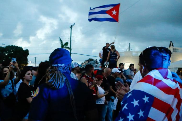 With some holding and waving Cuban and U.S. flags, demonstrators protest against the Cuban government July 11 in Miami. Thousands of Cubans across the island-nation took part in rare protests against the communist government, marching through several towns chanting, 'Down with the dictatorship,' and 'We want liberty.'
