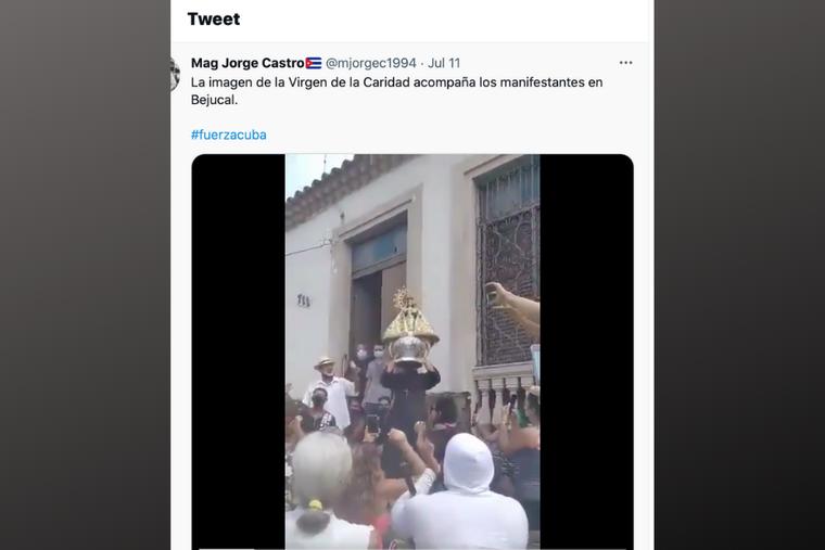 A local Cuban captures his fellow countrymen cheering and praying as a priest hoists a statue of La Virgen de la Caridad amid protests in Cuba.