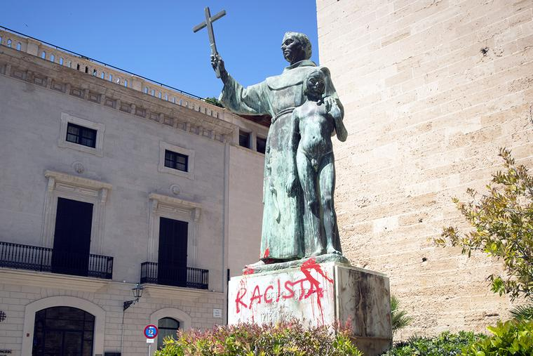 """A statue of St. Junípero Serra is pictured June 22 in Palma de Mallorca, Spain, after it was sprayed with graffiti reading """"Racist."""""""