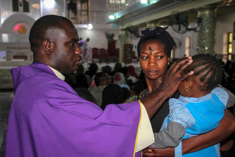 A priest signs the forehead of a child as catholics take part in the Ash Wednesday celebration at the St. Patrick cathedral in Maiduguri on February 26, 2020.