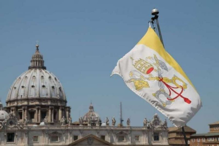 The flag of Vatican City with St. Peter's Basilica in the background.