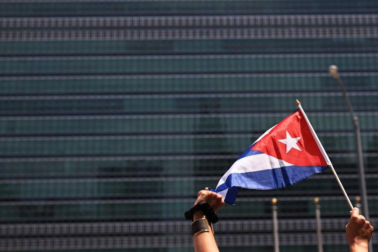 A person holds up a Cuban flag as people gather July 14 in front of the United Nations in New York City ; those gathered were calling for help for Cuban protesters. The island-nation protest has been the largest anti-government protest in decades.