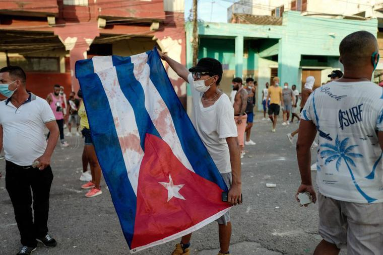 A man waves a Cuban flag during a demonstration against the government of Cuban President Miguel Diaz-Canel in Havana, on July 11, 2021 after  thousands of Cubans took part in rare protests against the communist government.