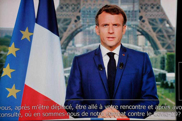 French President Emmanuel Macron is seen on a TV screen as he speaks during a televised address to the nation from the temporary Grand Palais in Paris on July 12. Macron announced that a 'COVID pass' will be needed in restaurants starting Aug. 1.