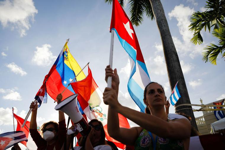 People hold Cuban, Peruvian and Venezuelan flags during a protest showing support for Cubans demonstrating against their government, at Versailles Restaurant in Miami, on July 18, 2021.