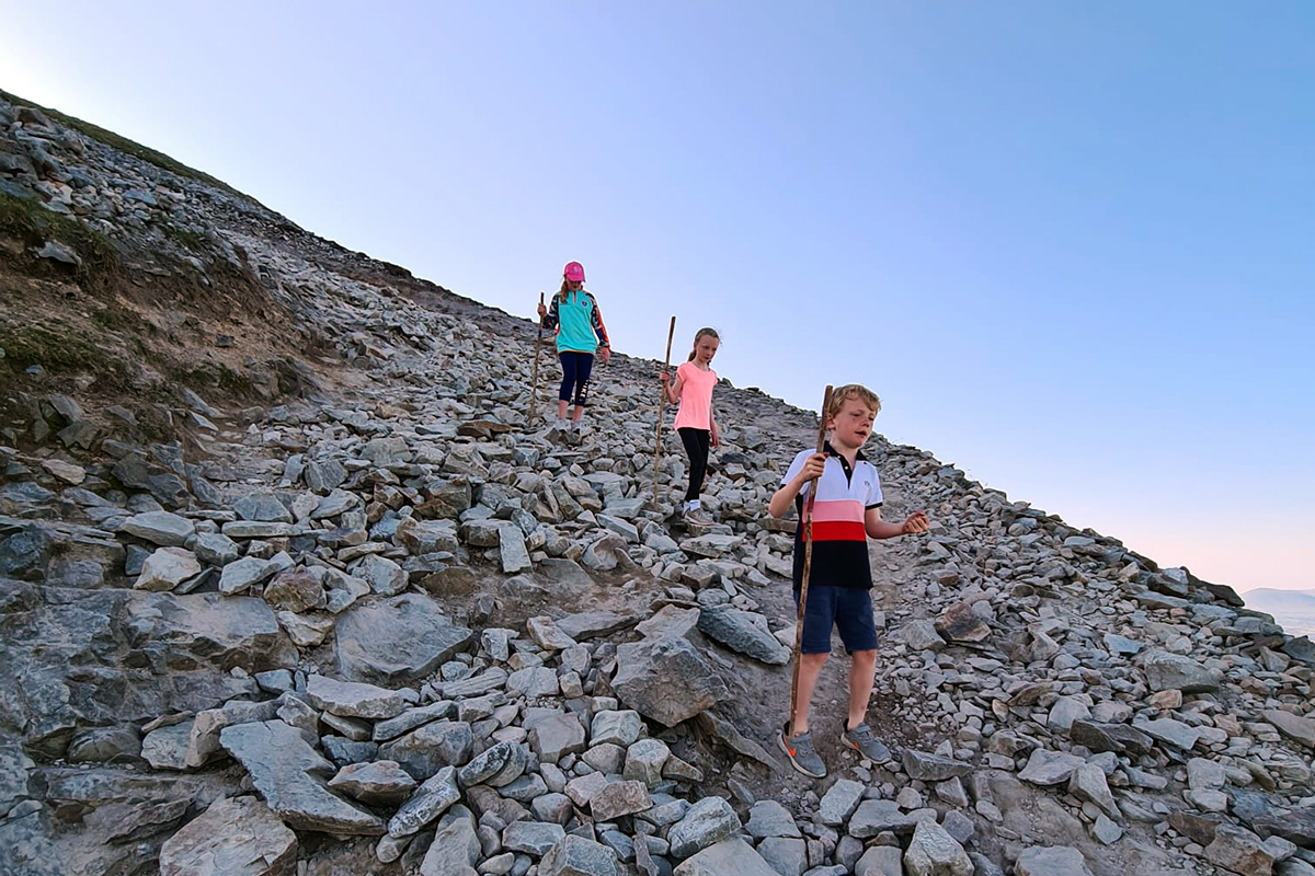 Pilgrims descend Croagh Patrick with a wooden staff to help navigate rough ground.