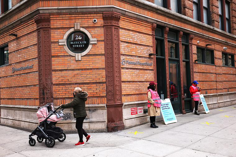 A woman pushes a stroller past the Planned Parenthood in the Financial District neighborhood of Manhattan on April 16.