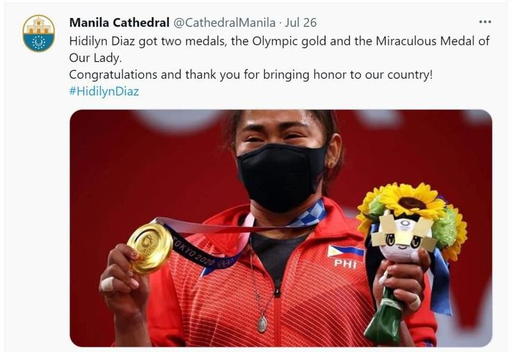 Olympian Hidilyn Diaz holds her gold medal and her Miraculous Medal after her victory, as shown in a tweet from the Manila Cathedral Twitter account.