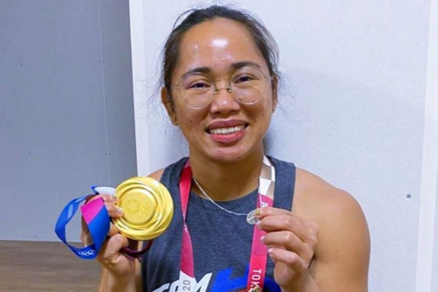 Filipina weightlifter Hidilyn Diaz proudly displays her Olympics gold medal and the Miraculous Medal, a devotional medallion depicting the Virgin Mary.