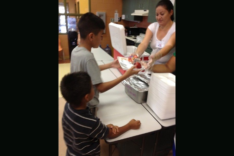 A woman offers lunch to migrant children amid the COVID pandemic in McAllen, Texas.
