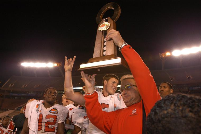 Coach Chuck Amato celebrates the Wolfpack's 56-26 win over Kansas in the 2003 Mazda Tangerine Bowl with WR Jerricho Cotchery and QB Philip Rivers.