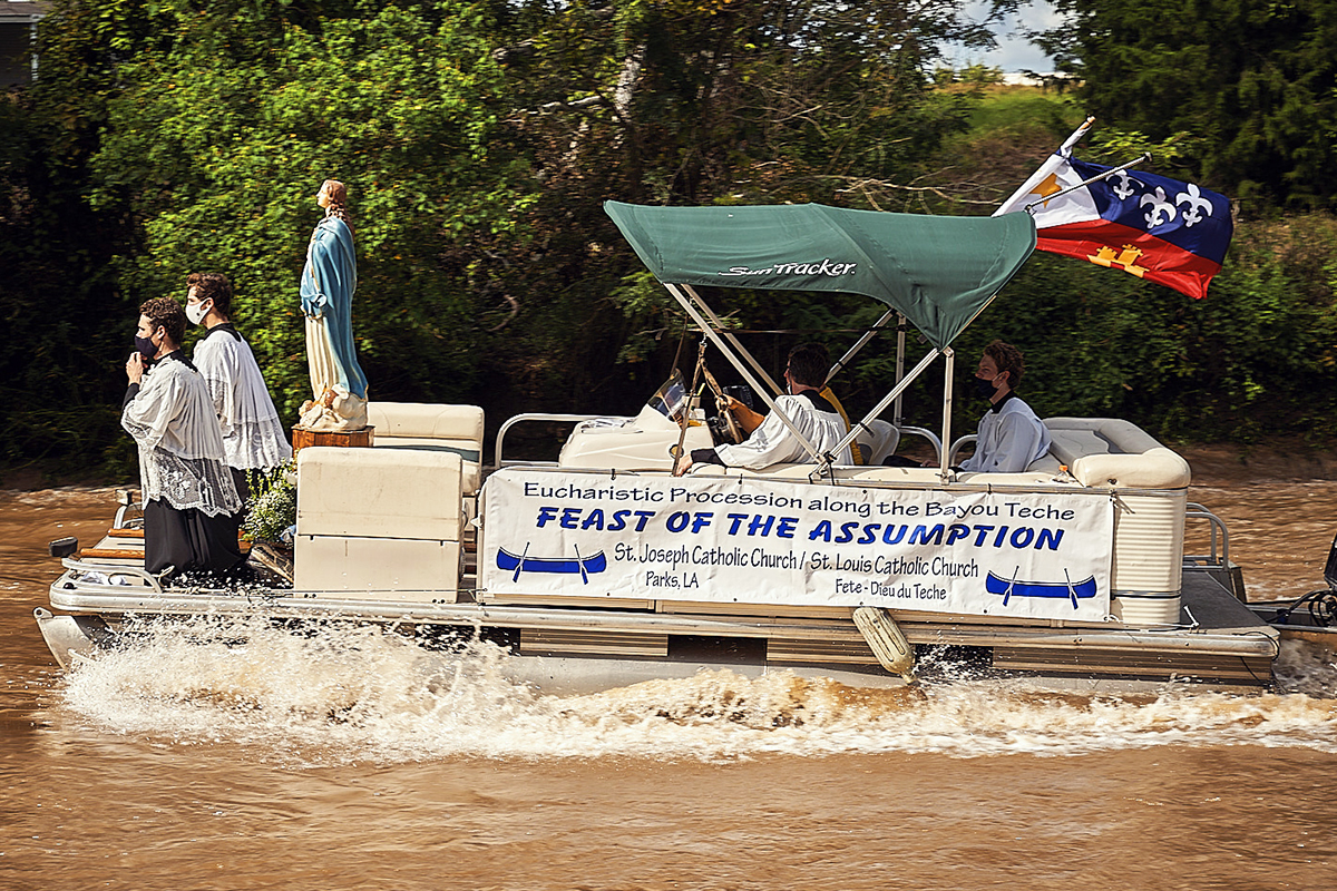 A boat carries a statue of Our Lady down the Bayou Teche.