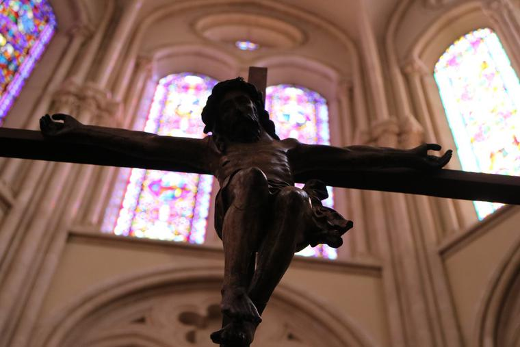 The crucifix is seen against a backdrop of stained glass in St. Ignatius Church in Paris.