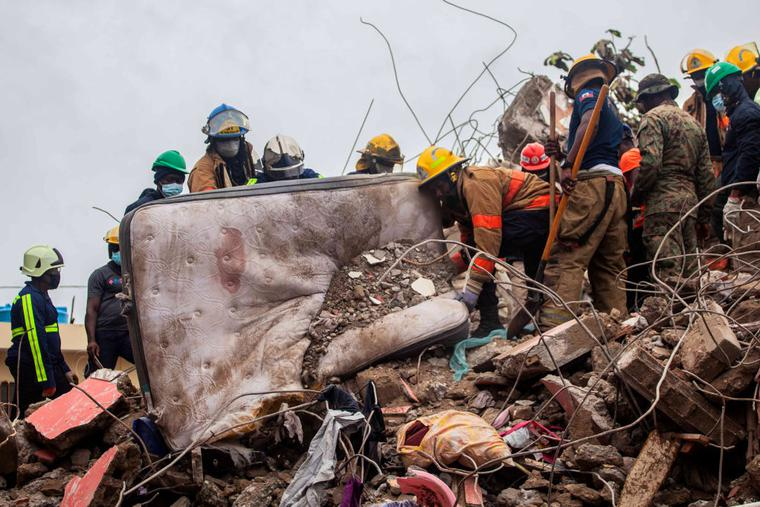 Firefighters remove debris in search of survivors after a 7.2-magnitude earthquake struck Haiti and as tropical storm Grace moves over Jamaica on August 17, 2021 in Les Cayes, Haiti.