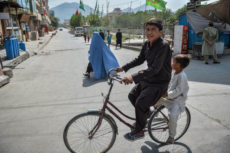Boys ride a bicycle along a road in Kabul on August 19, 2021, amid the Taliban's military takeover of Afghanistan.