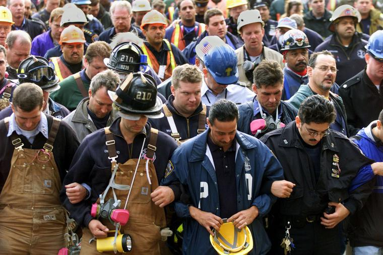 Firemen, police officers, and workers lock arms while observing a moment of silence during a short interfaith memorial service held at the World Trade Center disaster site 11 October, 2001 in New York.