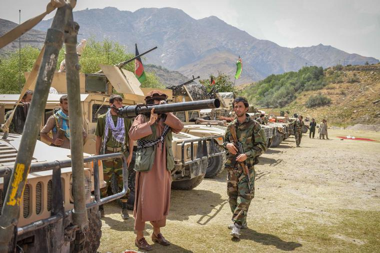Afghan armed men supporting the Afghan security forces against the Taliban stand with their weapons and Humvee vehicles at Parakh area in Bazarak, Panjshir province on August 19, 2021.