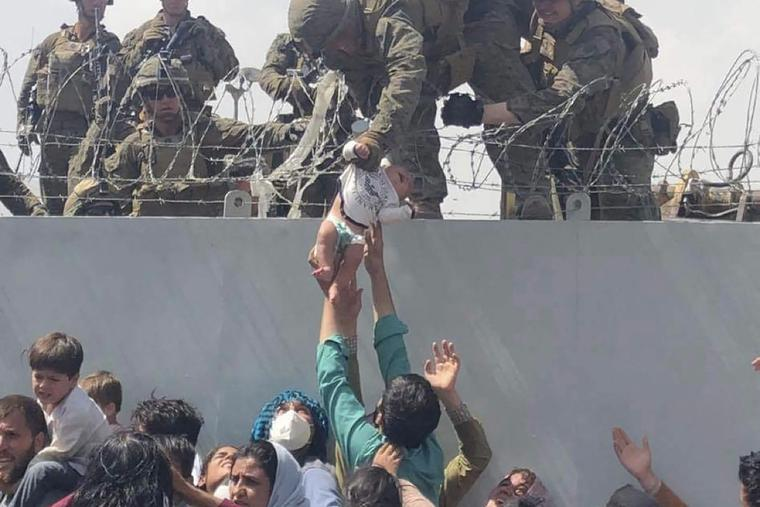 This image made available to AFP on August 20, 2021 by Human Rights Activist Omar Haidari, shows a US Marine grabbing an infant over a fence of barbed wire during an evacuation at Hamid Karzai International Airport in Kabul on August 19, 2021. The baby has been reunited with his family after being treated for an illness at a Kabul hospital.