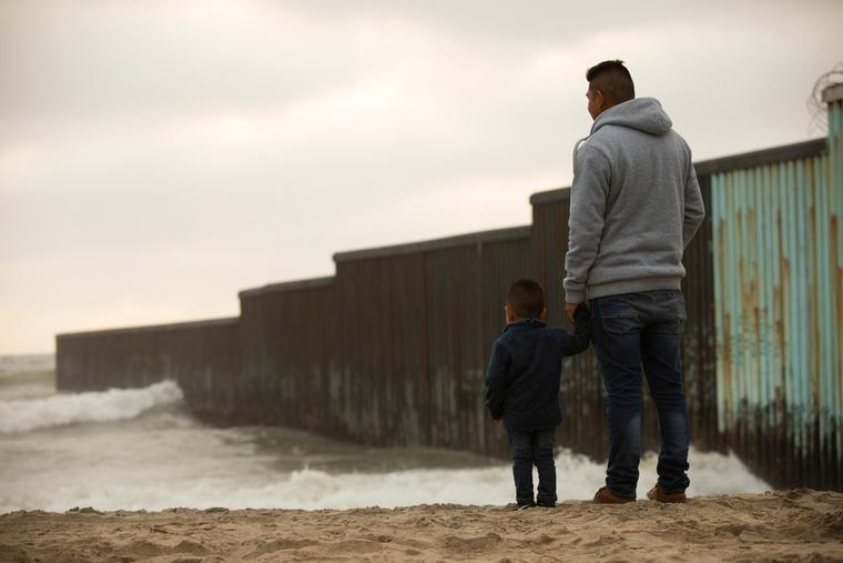 A father and son stand in front of the USA Mexico border wall at Tijuana.