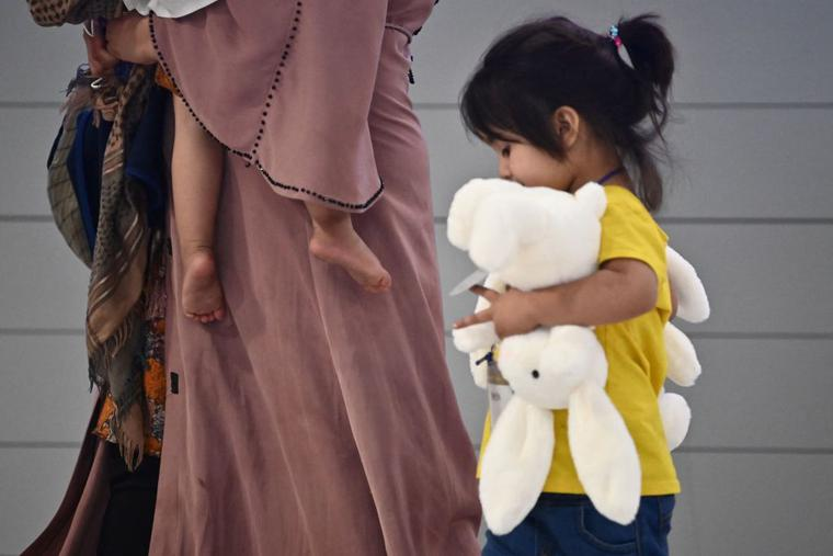 Afghan evacuees arrive at Incheon International Airport outside Seoul on August 26, 2021, following their departure from Kabul via Pakistan.