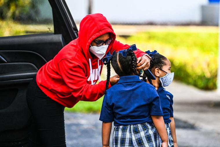 A mother adjusts the facemask of her child as she enters St. Lawrence Catholic School on the first day of school after summer vacation, north of Miami, on Aug. 18.