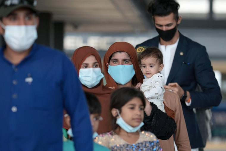 Refugees walk through the departure terminal to a bus at Dulles International Airport after being evacuated from Kabul following the Taliban takeover of Afghanistan on Tuesday. The Department of Defense announced yesterday that the U.S. military had completed its withdrawal from Afghanistan, ending 20 years of war.